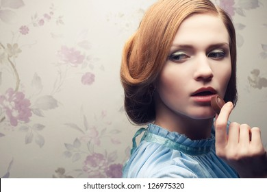 Vintage portrait of a glamorous red-haired (ginger) girl in blue dress eating chocolate candy. Close up. Copy-space. Studio shot