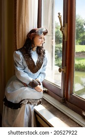 """Vintage portrait of a victorian lady standing by a castle window. Shot in the antique castle """"Den Brandt"""" in Antwerp, Belgium (with signed property release for the Castle interiors)."""