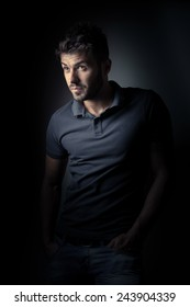 Vintage portrait of young male model over black background with a polo shirt