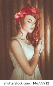 vintage portrait of young woman at the wooden background with flower ringlet