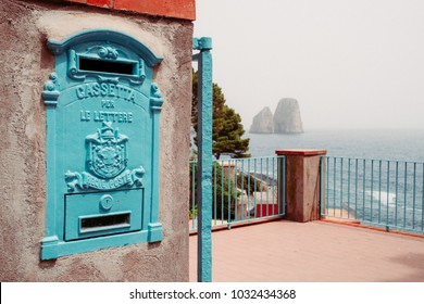 """Vintage post box with words """"Box for letters, Regie post"""" written on it with Faraglioni rocks on the background in Capri island, Campania, Italy."""