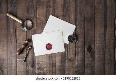 Vintage postal stationery. Blank envelope, sealing wax, stamp, spoon, magnifier, compass and postcard on wood background. Responsive design mock up. Flat lay.