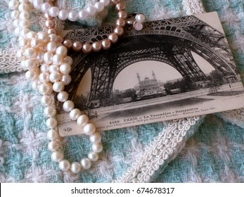 Vintage postcard of 1911 with the image of the Eiffel Tower, beads from pearls  on the background white and turquoise hand weaving matting tweed fabric texture. Chanel style concept. Closeup