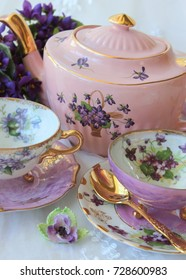 Vintage purple violets teacups and pink teapot with gold teaspoons, high tea party.