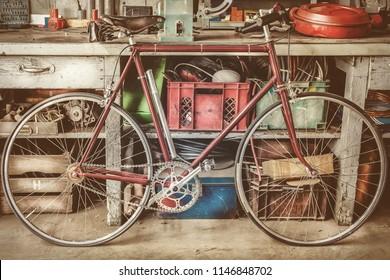 Vintage racing bycicle in front of an old work bench with tools in a garage