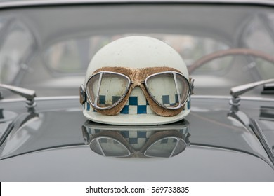 Vintage racing helmet and goggles sitting on the hood of a vintage Italian sports car.