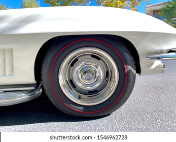 Vintage radial red line car tire on a restored white automobile. Tubeless racing sport tyre with shiny hubcap on a sunny day.