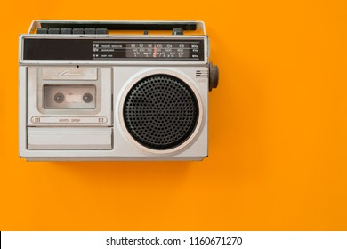 vintage radio and cassette player on colour background, flat lay, top view. retro technology