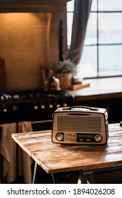 a vintage radio player stands on a wooden table in the apartment. Daylight from the window illuminates the room. Cozy kitchen playing classical music.