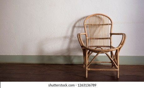 Vintage rattan chair on wooden floor against white concrete wall background