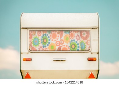 Vintage rear of a caravan with colourful seventies flower curtains