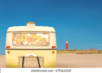 Vintage rear of a caravan in two tone yellow and white in front of a Dutch beach on the island of Texel