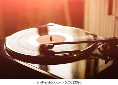 Vintage record player with vinyl disc, close-up. ray from the sunset