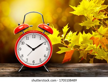 Vintage red alarm clock against the background of yellow autumn maple leaves. Return to wintertime. The old clock next to autumn leaves on a wooden table in front blurred background with copy space.