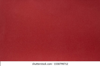 A vintage red background with a crisscross mesh pattern and grunge stains