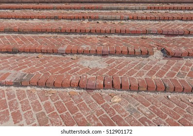 Vintage red brick stairway with beach sand and leaves.