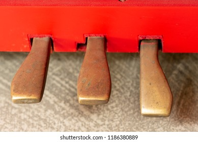 Vintage red classical grand piano. the piano pedals of antique key music instrument front view composition closeup