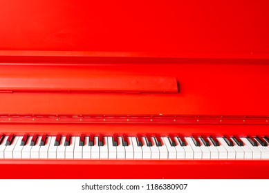 Vintage red classical grand piano. Black and white keys. The keyboard of antique key music instrument front view composition closeup