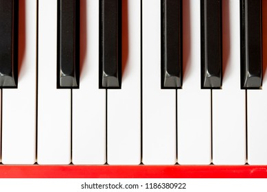 Vintage red classical grand piano. Black and white keys. The keyboard of antique key music instrument top view composition closeup