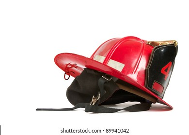 Vintage red fire fighters helmet with dark grey ear flaps, straps, black leather crest, brass trim, and gold stitching. Table top still life on white background, horizontal format with copy space.