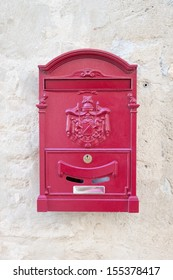 vintage red metal mail box on the plaster wall