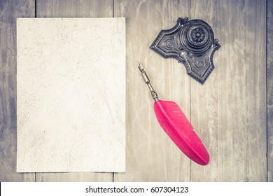 Vintage red quill pen and inkwell, old handmade paper sheet blank on wooden desk background. Retro style filtered photo