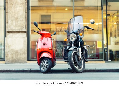 Vintage red scooter and black motorcycle parked on road empty italian city street. Symbol of couple, love, relations of man and woman. Advenure and travel lifestyle. Italian culture scenic background
