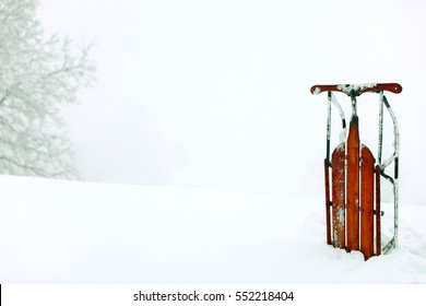 A vintage red sled in the snow.  A photography image for printing or adding studio portraits.