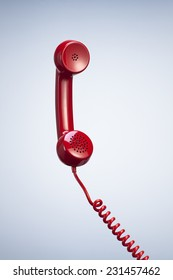Vintage Red Telephone Receiver with Hanging Cable isolated Beautiful Studio Background. Top View with Copy Space for Text