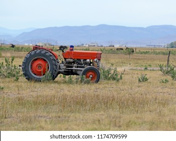 Vintage red tractor on farm in rural environment