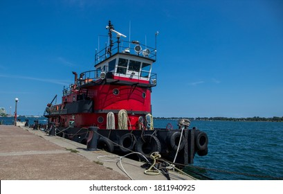 Vintage red tug boat staying in the harbour of city