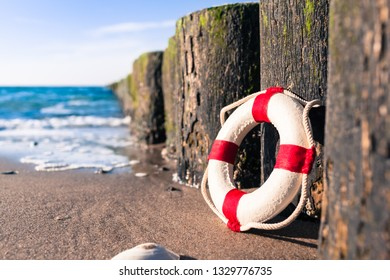 Vintage red and white miniature life buoy at row of groynes on sandy shore of baltic sea (copy space)