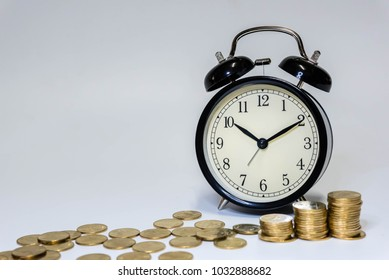 Vintage retro alarm clock and stack of coins to represent It's time to do money saving for retirement planning as concept.