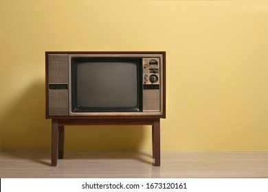 Vintage, Retro, Ancient old tv wooden cabinet stands on the floor with yellow concrete wall background.
