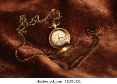 Vintage retro antique gold bronze watch clock with hurt on royal velvet brown background