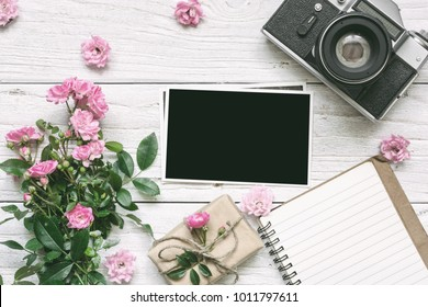 vintage retro camera and pink rose flowers bouquet with blank photo frame, lined notebook and gift box. holiday background. top view. flat lay. vintage toning