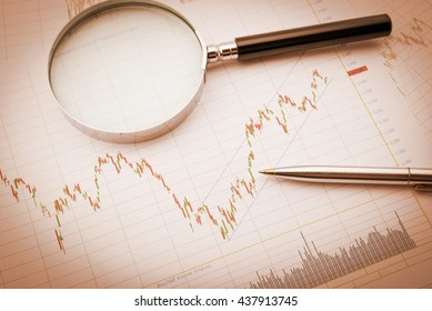 Vintage / retro color style : Blue ballpoint pen and a magnifier on a chart of financial instruments for stock / equity technical analysis. Charts include volume analysis, candlestick trend signal.
