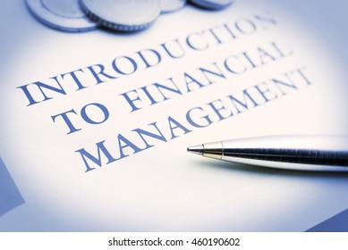 Vintage / retro color style : Blue ballpoint pen and coins on an introduction to financial management document. The basics that investors must learned or known before investing in any risky assets.