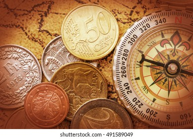 Vintage / retro color style : Pile of coins and a compass on an ancient treasure map. An idea of putting money / assets / portfolio in an assigned direction by diversifying products to minimize risk.
