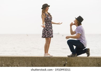 Vintage retro couple, man and woman enjoying their romantic date outside wearing fedora hats by seaside