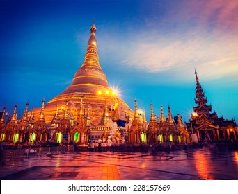 Vintage retro effect filtered hipster style image of Myanmer famous sacred place and tourist attraction landmark - Shwedagon Paya pagoda illuminated in the evening. Yangon, Myanmar (Burma)