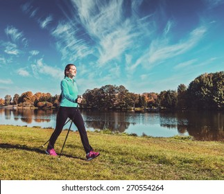 Vintage retro effect filtered hipster style image of nordic walking adventure and exercising - young woman hiking with nordic walking poles in park along river