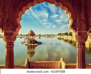Vintage retro effect filtered hipster style image of Indian landmark Gadi Sagar - artificial lake view through arch. Jaisalmer, Rajasthan, India