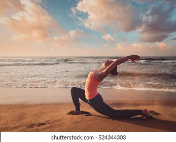 Vintage retro effect filtered hipster style image of Yoga outdoors - sporty fit woman practices yoga Anjaneyasana - low crescent lunge pose outdoors at beach on sunset