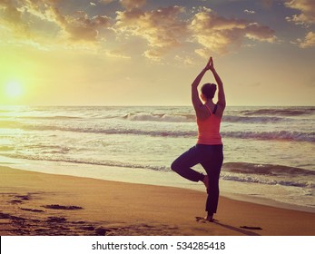Vintage retro effect filtered hipster style image of Yoga outdoors - sporty fit woman doing Hatha yoga asana Vrikshasana tre pose on tropical beach on sunset