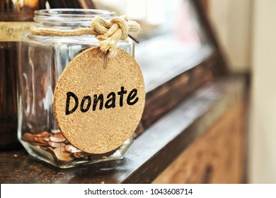 Vintage retro glass jar with hemp rope tie donate tag and few coins inside on wood counter with copy space. concept of raise donation, charity, help others.
