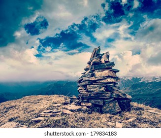 Vintage retro hipster style travel image of stone cairn in Himalayas mountains