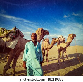Vintage retro hipster style travel image of Rajasthan travel background Indian man cameleer (camel driver) portrait with camels in Thar desert with grunge texture overlaid. Jaisalmer, Rajasthan, India