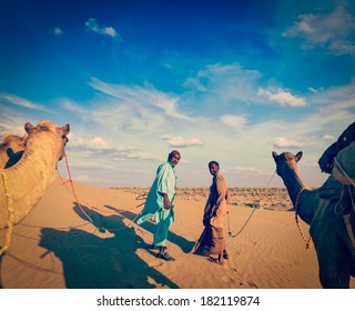 Vintage retro hipster style travel image ofvintage retro hipster style travel image of Rajasthan travel background - two indian cameleers (camel drivers) with camels.  Thar desert,  Rajasthan, India