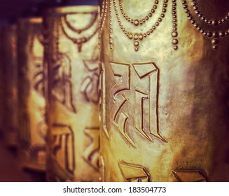 Vintage retro hipster style travel image of Tibetan Buddhist prayer wheels in Buddhism temple. Shallow depth of field. McLeod Ganj, HImachal Pradesh, India